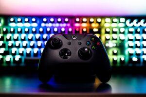 геймпад на фоне светящейся клавиатуры